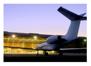 aerospace hangar with jet plane in front of it at night