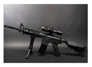 machine gun rifle sitting on a table with gray background